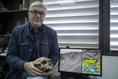 Fernando Muñiz, uno de los investigadores de las huellas de los neandertales, sostiene la reproducción de un cráneo de estos homínidos mientras muestra la huella hallada en Gibraltar.