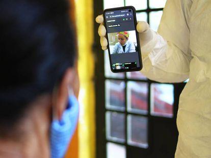 Una consulta médica con paciente y sanitaria comunicándose a través del teléfono móvil.