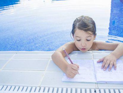 Una niña haciendo deberes en la piscina.