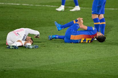 Lucas Vazquez  y Sergio Busquets, tras el choque en el que se lesionó el primero.