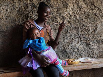 Una madre adolescente keniana almuerza con su bebé en brazos durante su pausa para el almuerzo en la Escuela Secundaria de Niñas Serene Haven, en Kiawara en Kieni, Nyeri, Kenia, el 10 de febrero de 2021.