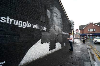 Un operario tapaba este lunes con cinta negra los insultos escritos en el mural de homenaje al jugador Marcus Rashford, en Mánchester (Inglaterra).