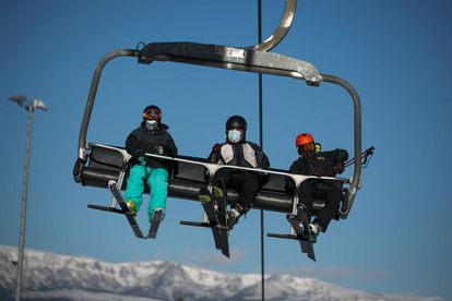 Tres esquiadores con mascarilla, en un telesilla de la Masella.