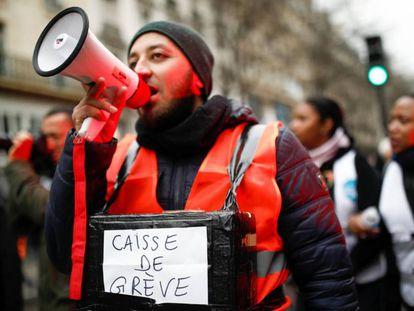Un manifestante de los trabajadores del transporte público, con un megáfono y una hucha solidaria para ayudar a los huelguistas. En vídeo, las claves de la huelga.