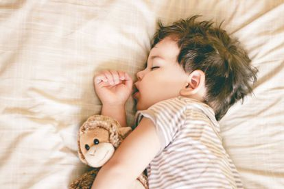 Niño duerme en su cama.