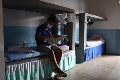 Un preso lee un diario de la Iglesia Universal en su celda en la Apac de Paço do Lumiar, una de las  50 prisiones de Brasil sin guardas ni armas donde más de 4.000 reclusos cumplen condena.