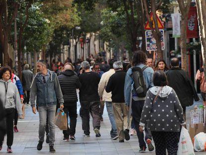 Varias personas pasean por Madrid.