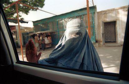 Una mendiga vestida con un burka pide dinero a los ocupantes de un coche en las calles de Kabul, en mayo de 2000..