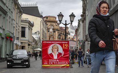 Varias personas caminan junto a un cartel de campaña del Partido Comunista, en una calle de Moscú, este miércoles.
