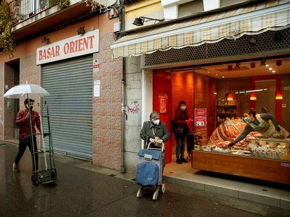 Varias personas pasan ante una tienda de alimentación en L'Hospitalet de Llobregat.