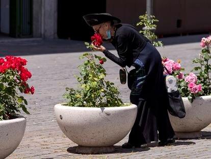 Una mujer se baja la mascarilla para oler unas rosas en Roma, el pasado mayo, en pleno confinamiento.