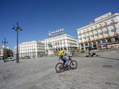 Un 'rider' de Glovo circula por la Puerta del Sol el 4 de abril.