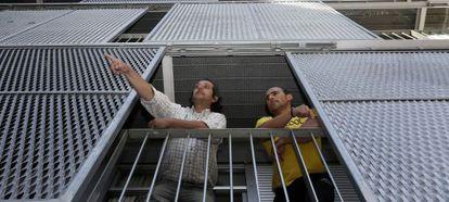 Abel (derecha) y su vecino Juan Andrés, en la terraza del piso de este último, en la calle del Pinar de San José en el Ensanche de Carabanchel.