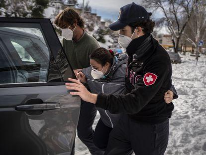 """Miguel Benzo (gorra) y Rodrigo Álvarez de Toledo ayudan este domingo a Ana González, """"Triana"""" a subir a un Land Rover para llevarla al Hospital de La Paz, en Madrid."""