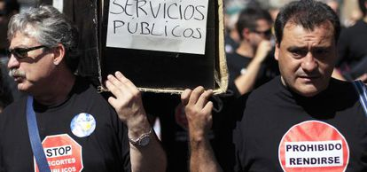 Dos funcionarios municipales cargan el féretro de los servicios públicos.