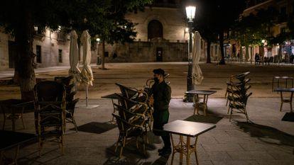 Un camarero recoge la terraza de un bar en la plaza de la Paja de Madrid.