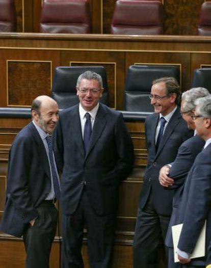 Gallardón conversa en el hemiciclo con Rubalcaba en presencia de otros diputados.