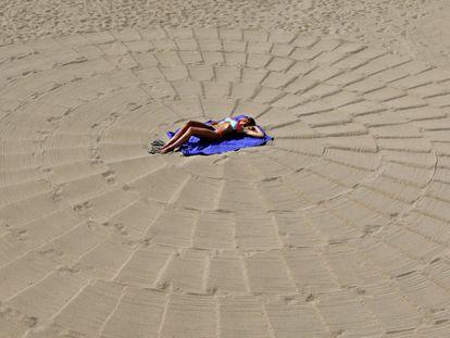 Una mujer toma el sol en una playa en Cannes, Francia.