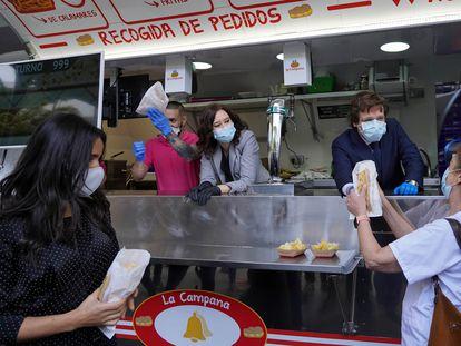 Ayuso y Almeida entregan bocadillos de calamares, durante la clausura del hospital de Ifema.