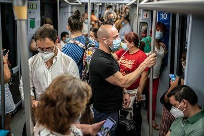 El metro de Madrid, abarrotado en algunos momentos. Decenas de pasajeros en los vagones de uno de los trenes que recorre la línea 10 del metro. En las estaciones se puso en marcha un sistema de cierre de tornos para tratar de evitar aglomeraciones.
