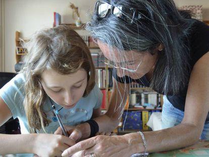 Una madre ayuda a su hija con los deberes.
