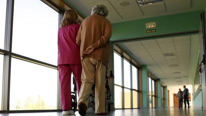 Una sanitaria acompaña a una paciente en el Centro de Referencia Estatal de Alzhéimer y otras Demencias de Salamanca.