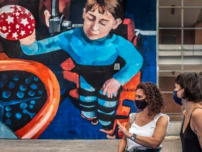 La científica Elena García Armada (de blanco) creadora del primer exoesqueleto biónico para niños, con la artista del mural, Sara Mono.