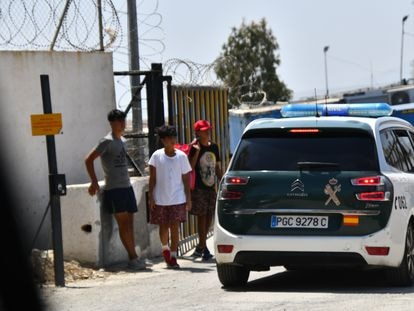 Menores alrededor de la entrada del centro de acogida de Piniers hablan con la Guardia Civil.