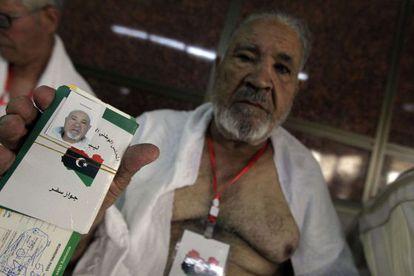 Un libio muestra su nuevo pasaporte, con la nueva bandera del país.