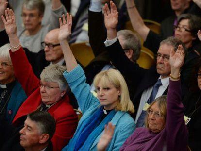 Miembros del sínodo de la Iglesia de Inglaterra votan a mano alzada sobre la ordenación de mujeres obispo, en Londres.