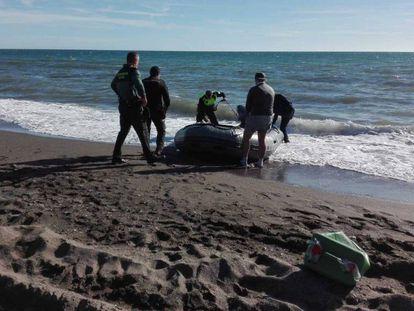 Agentes de la Guardia Civil y la Policía Local, con la patera que este sábado ha llegado a Vélez-Málaga.
