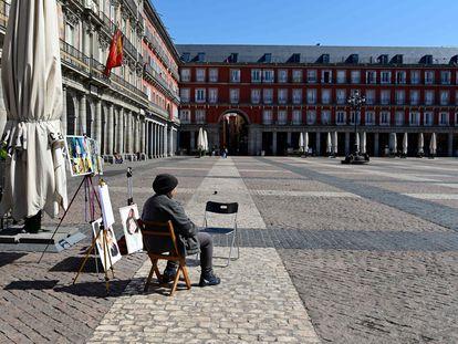 Un caricaturista espera a que llegue algún cliente en la Plaza Mayor de Madrid.