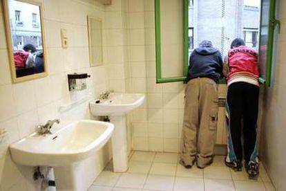 Dos adolescentes, en los lavabos del centro al que asisten a una terapia de ayuda contra el consumo de <i>hachís.</i>