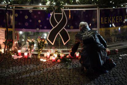Una mujer enciende una vela en el árbol de Navidad cerca de la Plaza de Brandenburgo, en memoria por las víctimas del atentado, este martes.