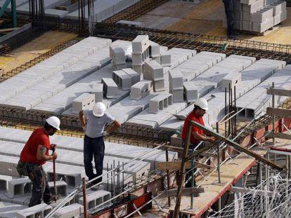 Trabajadores de la construcción levantan un edificio en Bilbao.