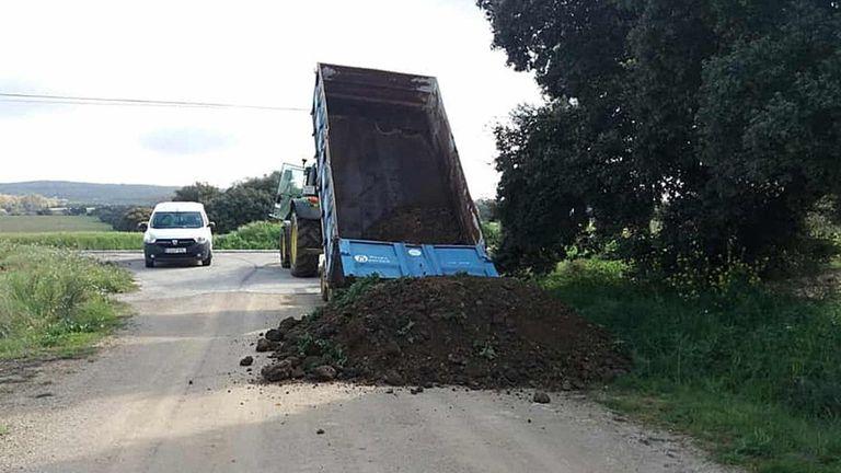 Un camión vuelca arena para cerrar uno de los accesos de Setenil de las Bodegas (Cádiz).