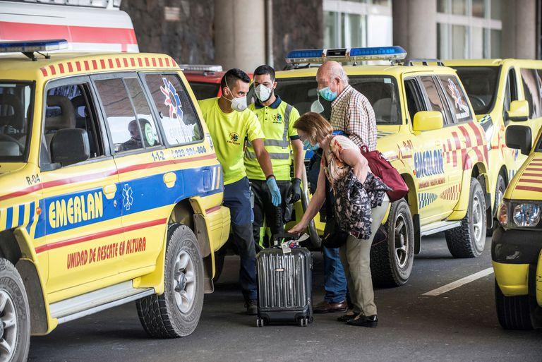 Dos viajeros reciben asistencia de los servicios de emergencias tras desembarcar en Lanzarote del vuelo procedente de Madrid en el que uno de los ocupantes ha dado positivo en covid-19.