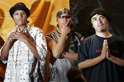 Tres miembros de Reyes y Reinas Latinos, el nuevo nombre adoptado por la banda juvenil Latin Kings, posan hoy ante su bandera.