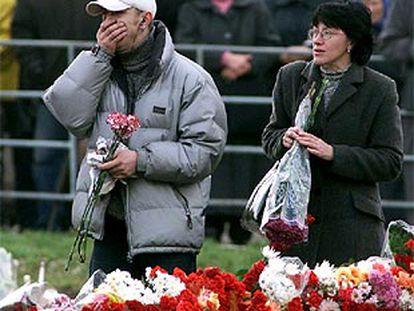 Dos ciudadanos colocan flores en el exterior del teatro moscovita donde se produjo el secuestro.