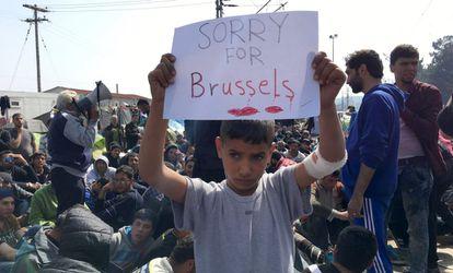 """Un niño refugiado enseña el martes una pancarta con el mensaje """"Lo siento por Bruselas"""" cerca de frontera greco-macedonia."""