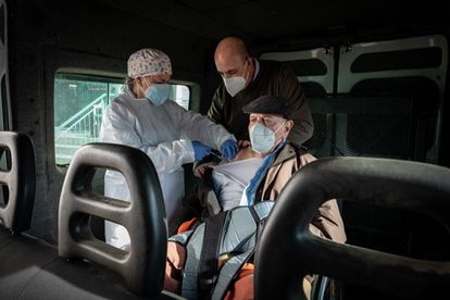 Lorenzo García, de 93 años, recibe la primera dosis de la vacuna acompañado de su hijo Manolo, dentro de una furgoneta adaptada para silla de ruedas.