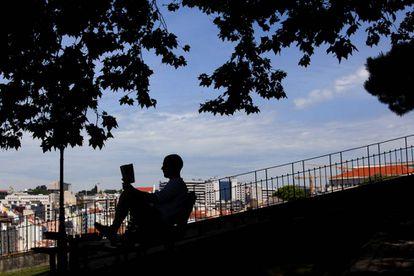 Un hombre lee en el jardín del Torel (Lisboa).