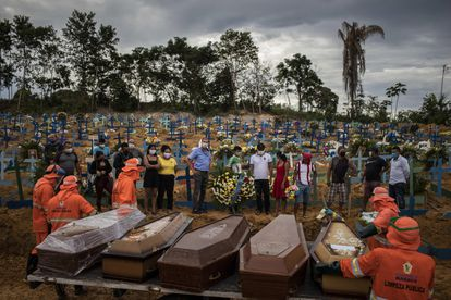 Un grupo de personas asiste a un sepelio en una tumba colectiva, el 23 de abril de 2020, en un área abierta en el cementerio Nossa Senhora Aparecida, en la ciudad de Manaos, Amazonas.