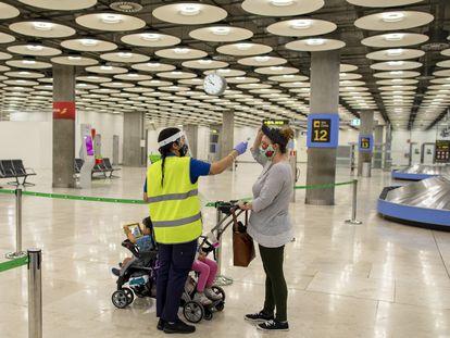 Una trabajadora toma la temperatura a una viajera en el aeropuerto de Madrid, en una imagen de 2020.