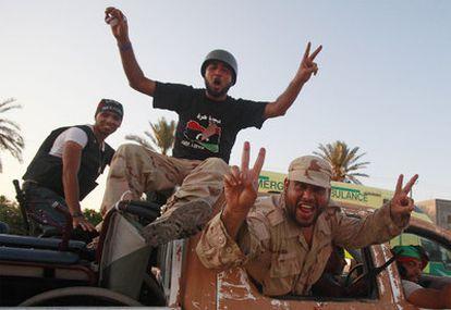 Combatientes libios rebeldes pasean por la localidad de Maia tras avanzar en las afueras de Trípoli.