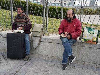 Antonio, el filósofo (izquierda), lee a Stevenson, Carlos a Grisham, mientras esperan que se abra el nuevo albergue de Ifema