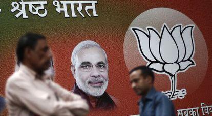 Varios hombres pasean frente a un cartel del candidato hindú, Narendra Modi.