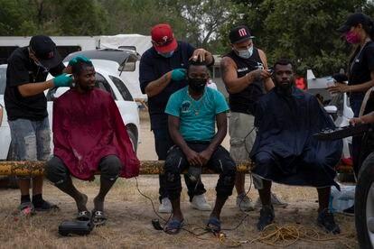 Migrantes haitianos reciben un corte de pelo gratuito en el parque donde se están albergando en Ciudad Acuña (México), este martes.