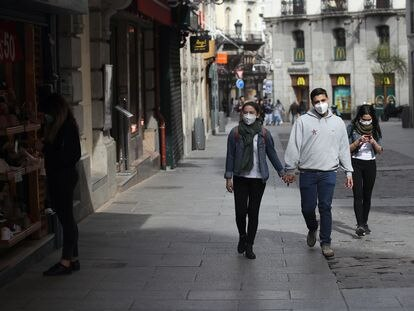 Varias personas protegidas con máscaras, en el centro de Madrid.