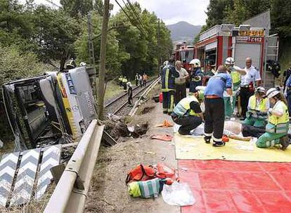 Los sanitarios atienden a uno de los heridos en el lugar del accidente.